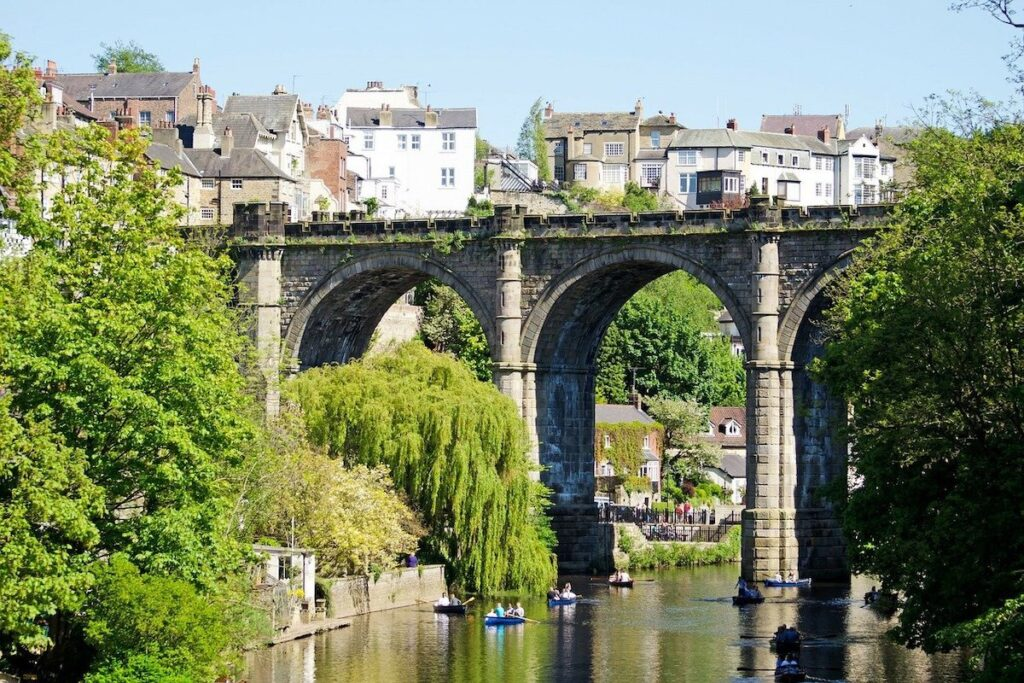 Knaresborough Viaduct with its mammoth arches across the river with people in rowing boats cruising on the water beneath it on a summers day.