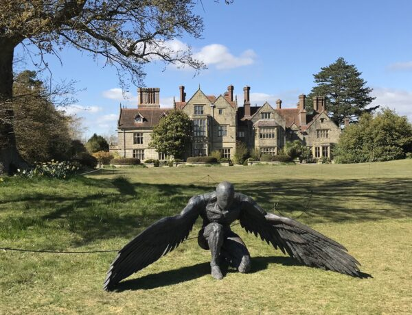 A sculpture of a man with wings kneeling on the lawn in front of Borde Hill House