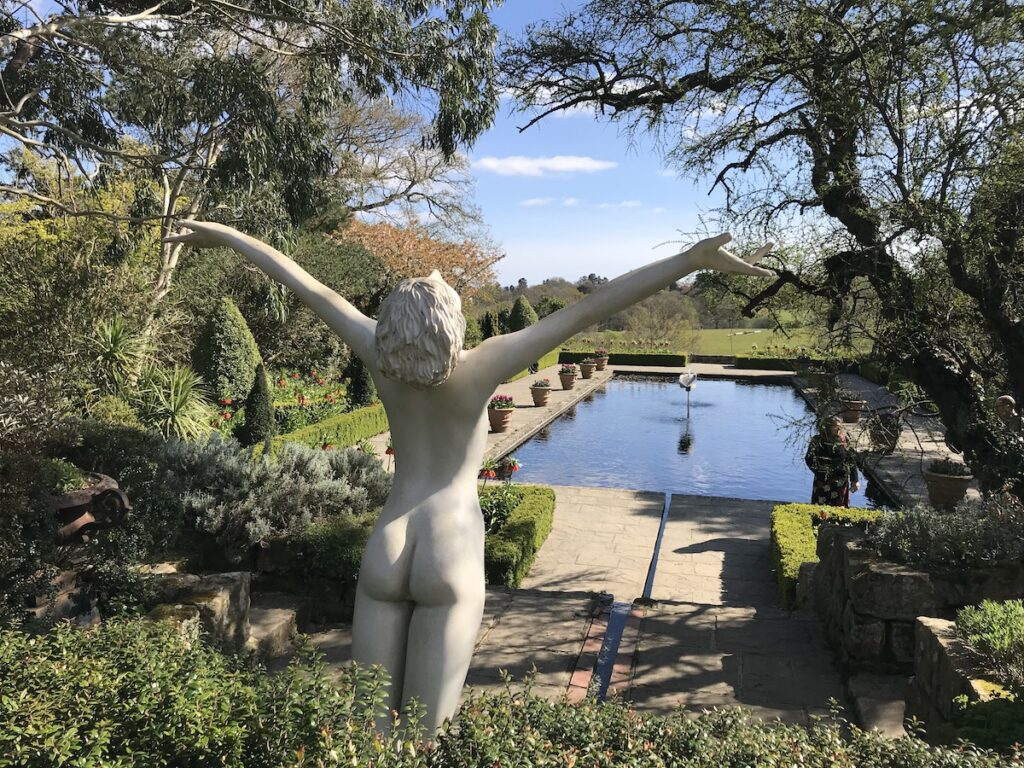 A sculpture of a nude lady overlooking the Italian pond and far views of the Sussex countryside