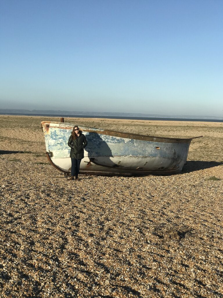 Angie standing next to an old blue fishing boat which is taller than her