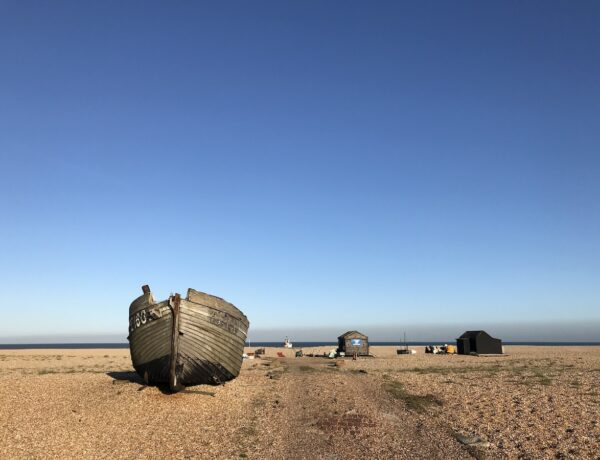 A wooden fishing boat sitting on a shingle beach in Dungeness