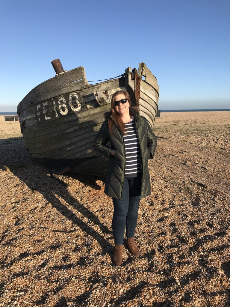 Angie standing next to an old fishing boat