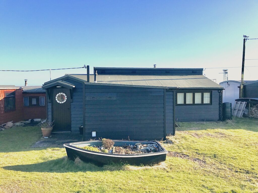 A grey cottage in Dungeness with a small wooden boat on the front lawn