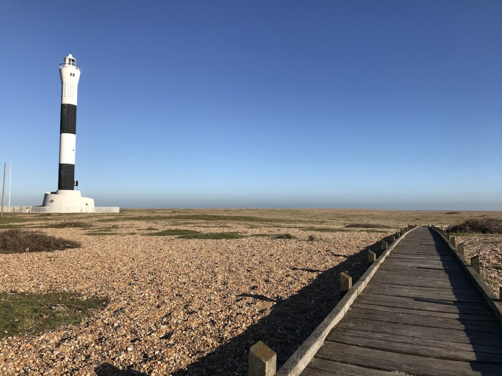 A view of the Dungeness lighthouse on the shingle beach with a boardwalk leading across the beach