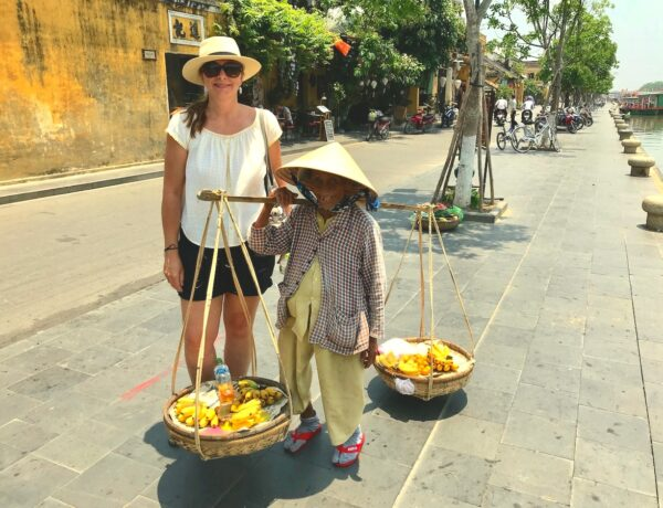 Angie standing next to a very small and old Vietnamese banana seller in a street in Hoi An.