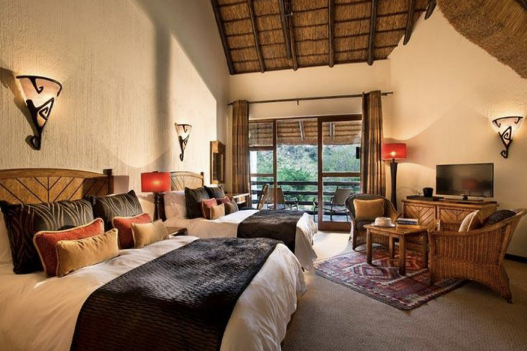 safari lodge bedroom with twin beds and a balcony with views to the bush