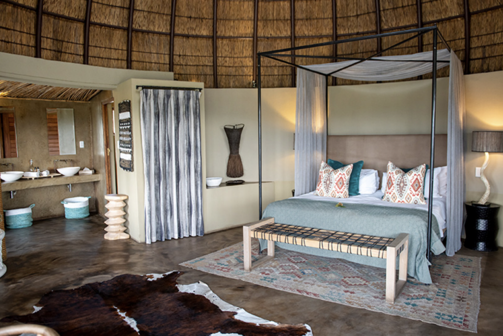 Interior of Kwena luxury lodge showing a four poster bed with pastel fabrics and an adjoining bathroom