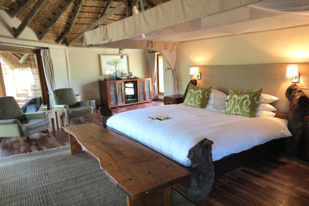 Safari Bedroom at Ulusaba Sabi Sand luxury safari camp . A wooden bed frame and wooden foot table bring the natural elements indoors.