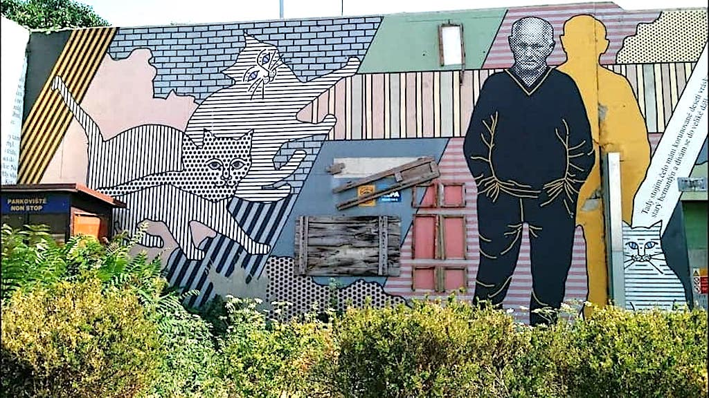 Street art on a wall depicting a man and cats