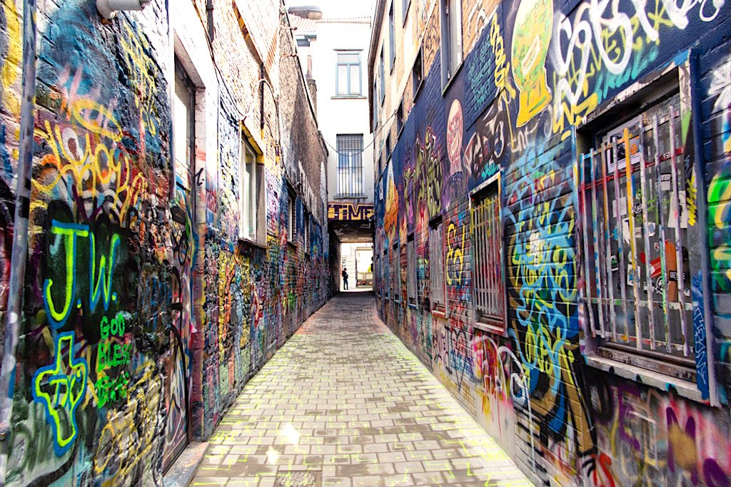 An alleyway with graffiti on its walls