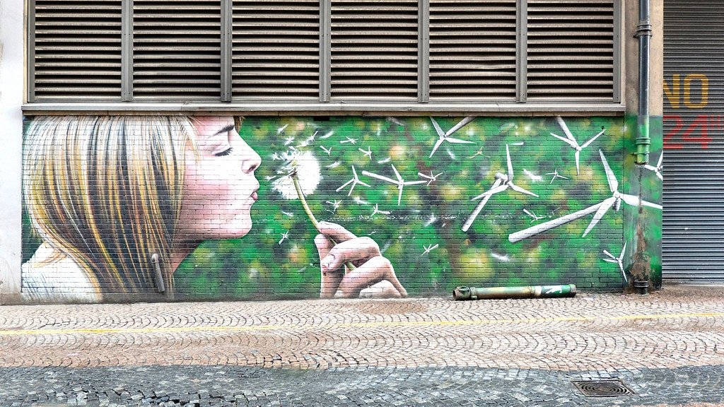 A mural depicting a girl blowing a dandelion