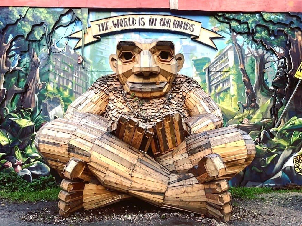 a troll made of wood infront of a street art mural