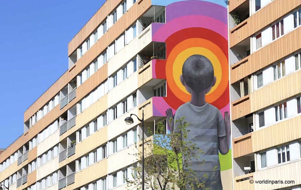 A building with street art of a yon boy and a rainbow