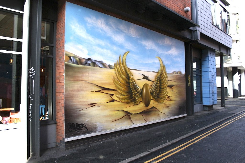 a mural depicting a golden egg with wings