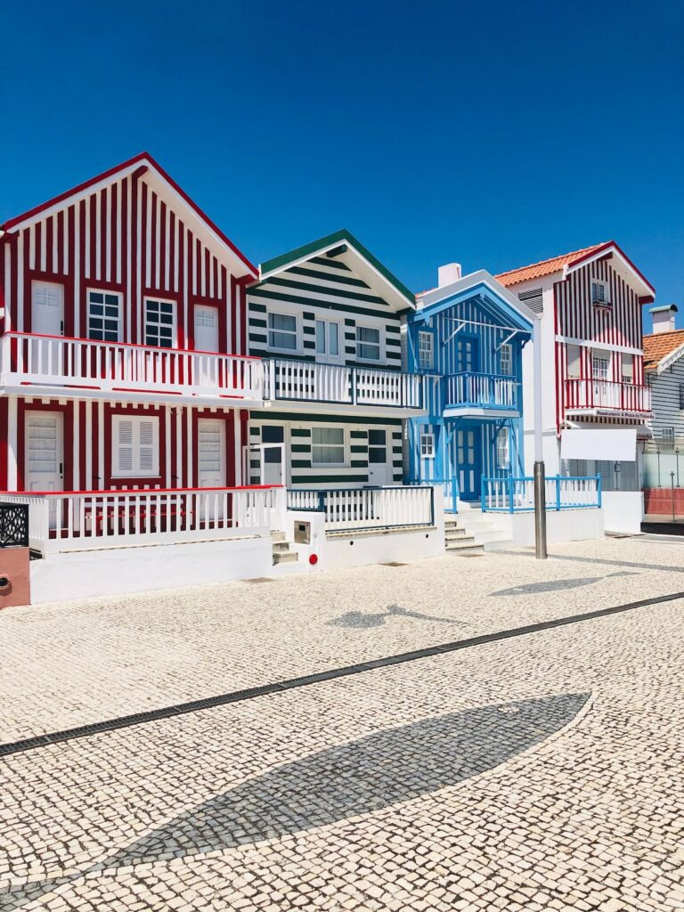 Candy Striped houses in red, blue and black lining the beach in Costa Nova