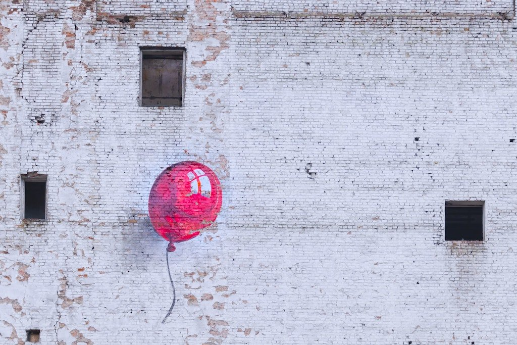 Street art depicting a red balloon painted on a white wall