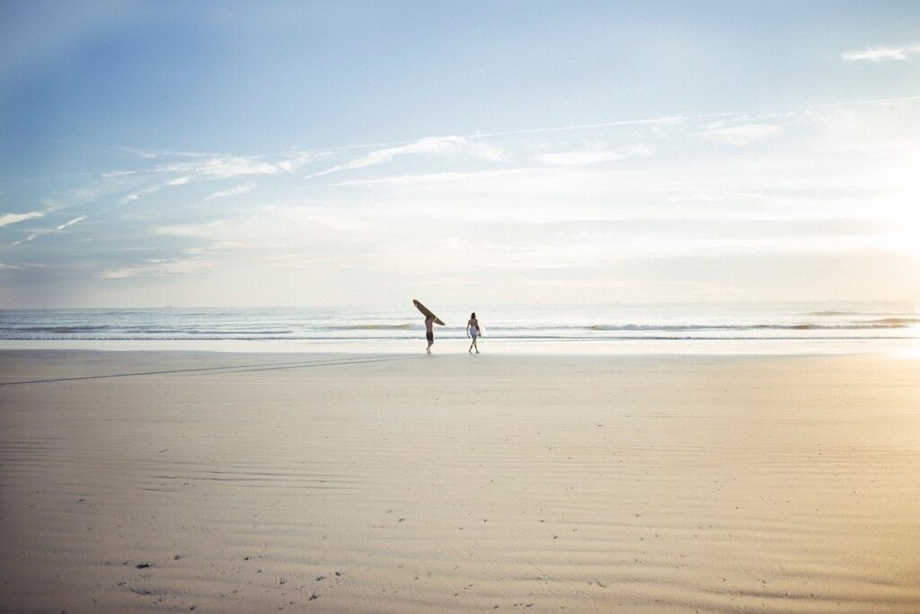 Two surfers walking into the sea carrying their surfboards in Portugal