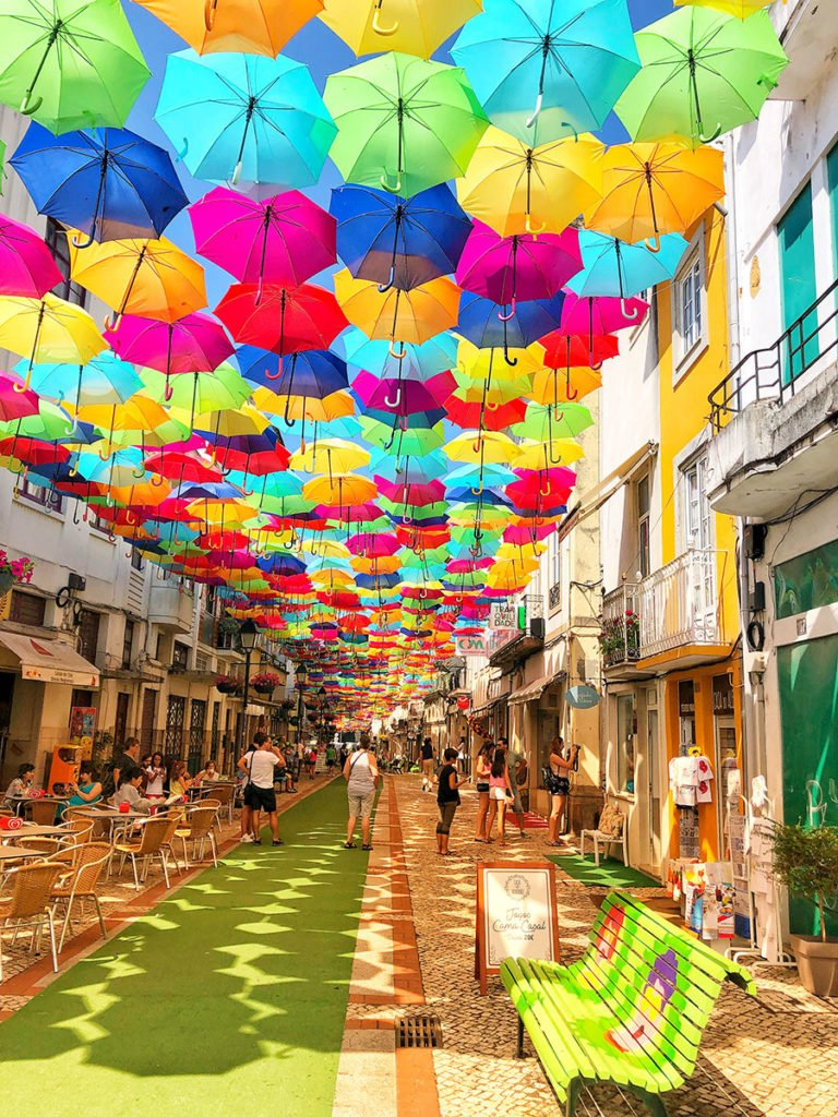 Brightly coloured umbrellas handing across the street in Portugal