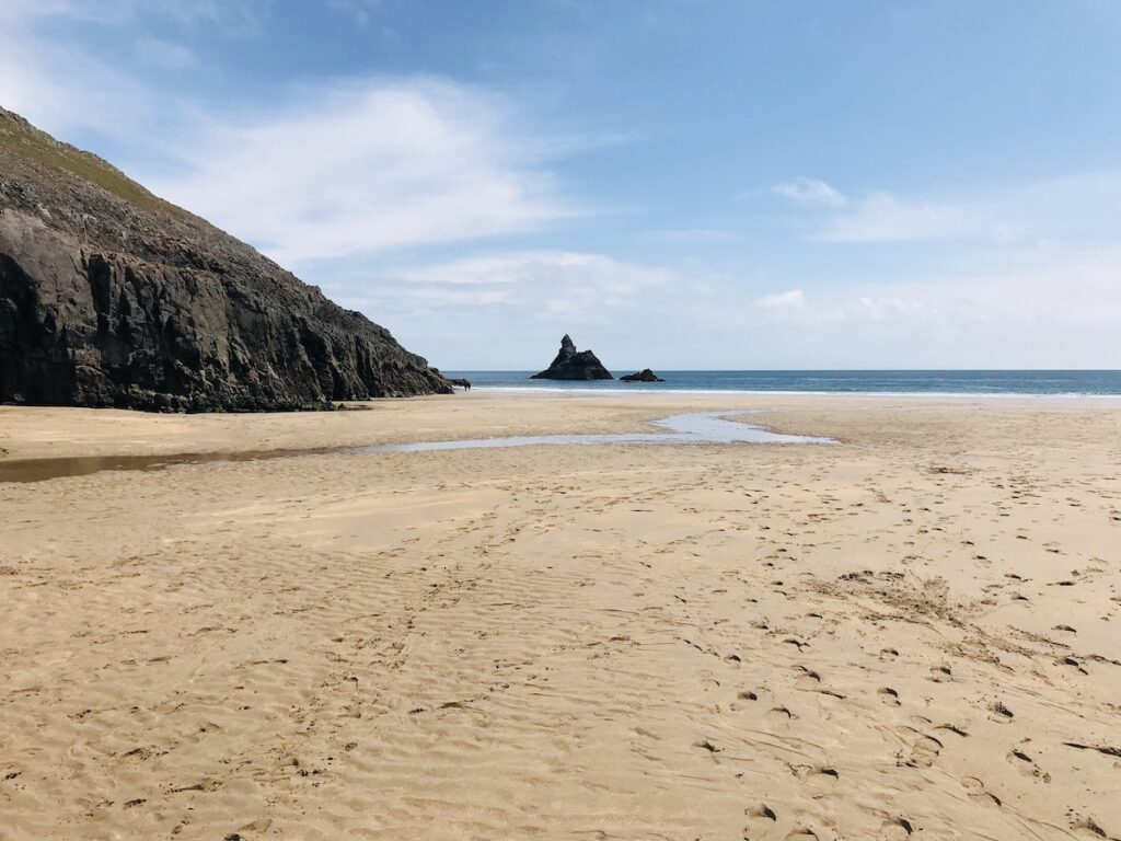 Sandy beach leading to the sea and church rock at Broad Haven South