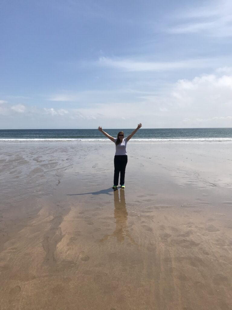 Angie standing on the beach with her arms in the air