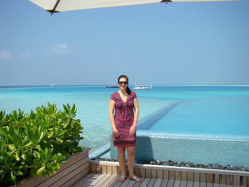 a woman standing in front of the infinity pool