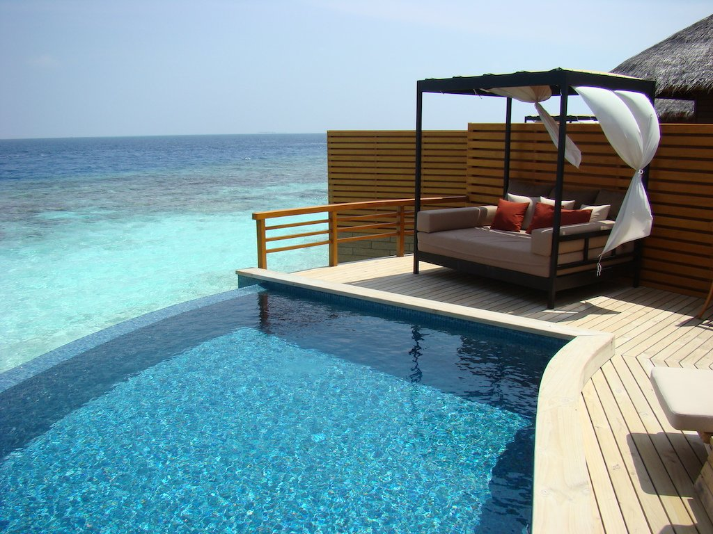 a pool and day bed on the decking of a villa