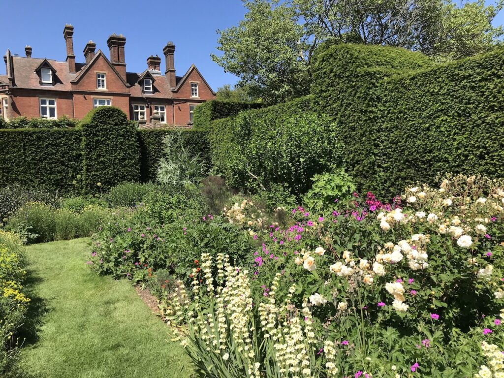 Doddington Place Gardens in Faversham with the Manor House in the foreground and flower borders in front
