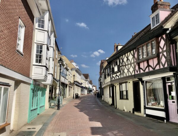 pastel coloured half-timbered buildings line the road in Faversham