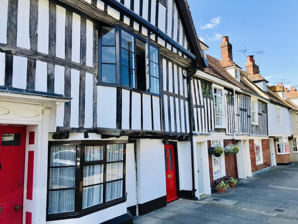 a row of white houses with black half timbers and red doors in faversham