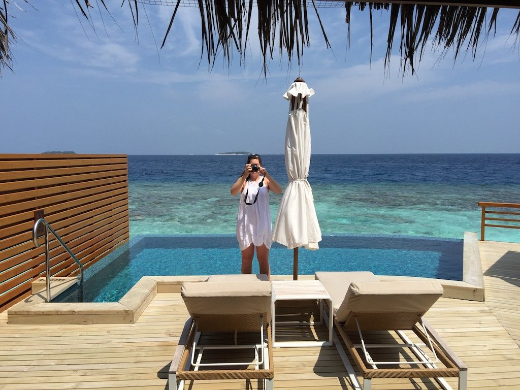 a lady standing by a pool taking a photograph