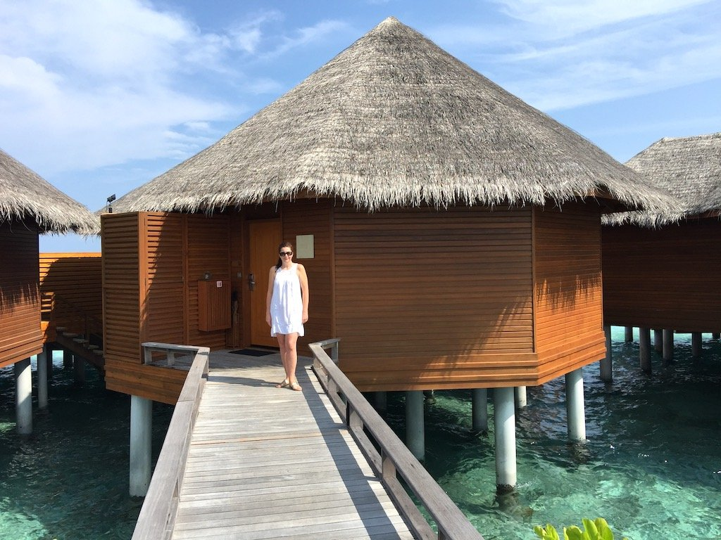 woman standing outside an overwater villa