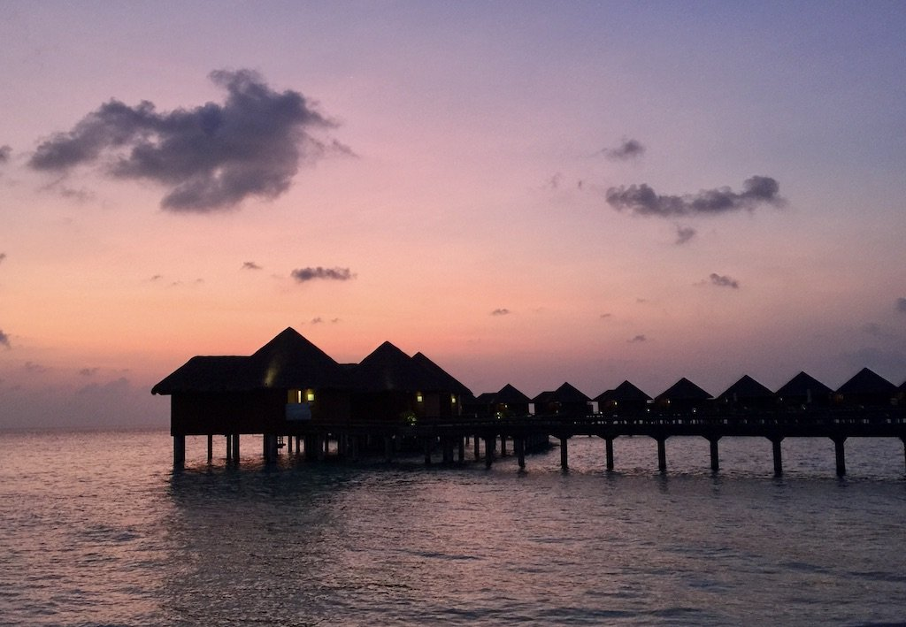 Overwater villas with a pink sky above at sunset