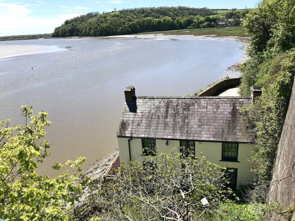 Dylan Thomas' Boathouse with the water of the Taf Estuary behind it