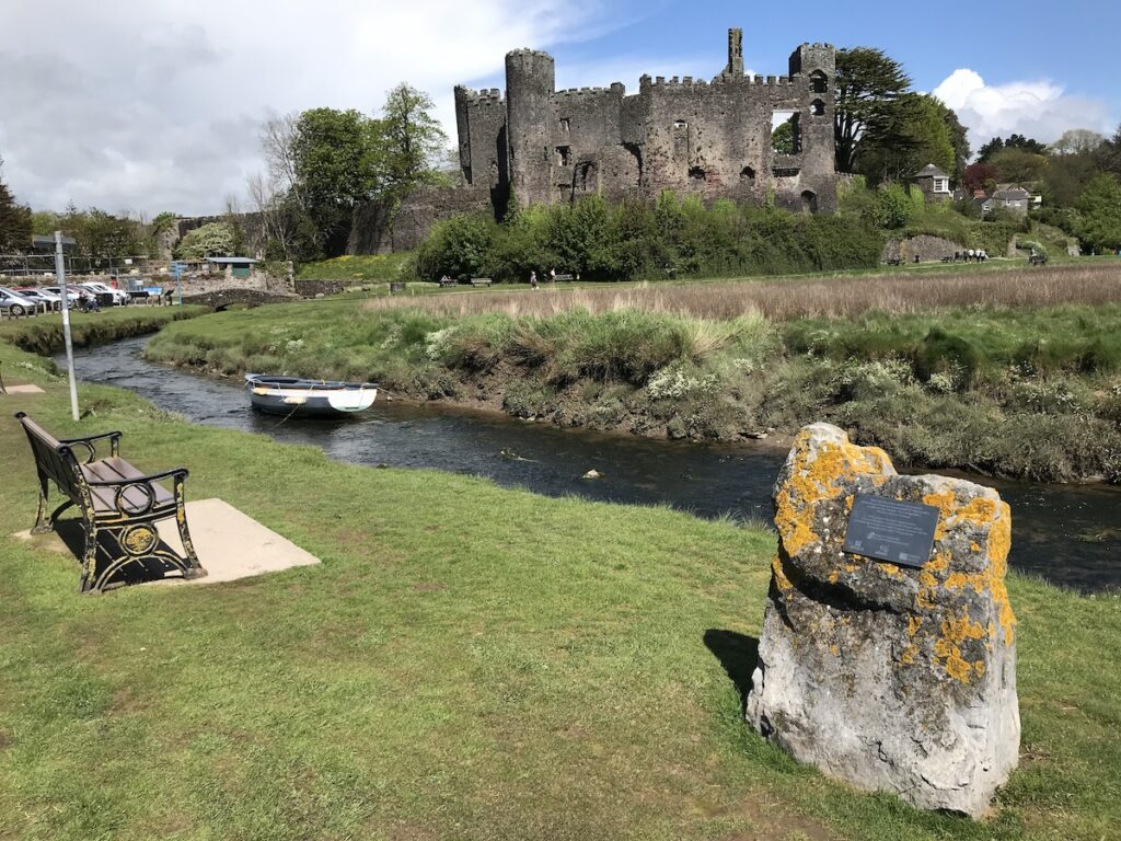Laugharne Castle with a wooden bench and marker in the forefront