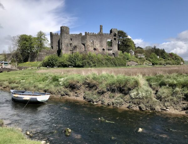 Laugharne Castle with a white rowing boat on a small river in the forefront