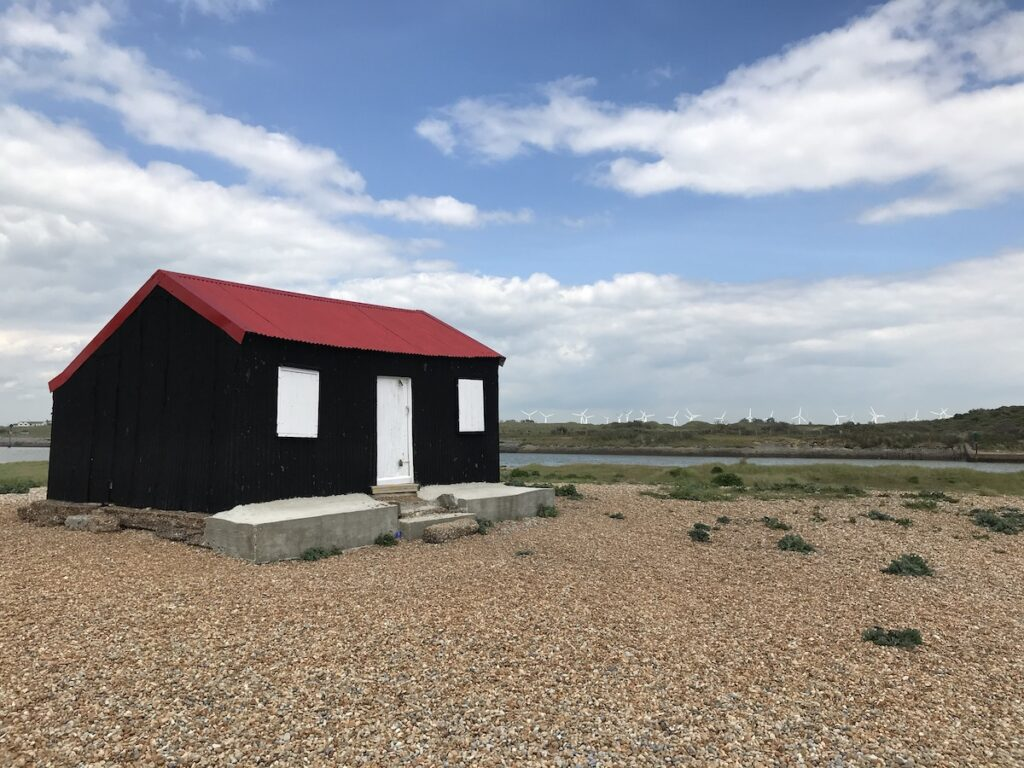 A black, white and red fishing hut on the beach in Rye Harbour