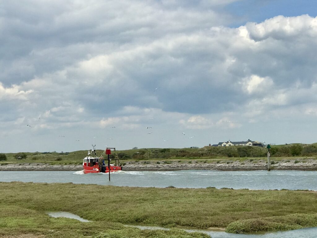 A red fishing boat on the River Rother in rye Harbour Nature Reserve