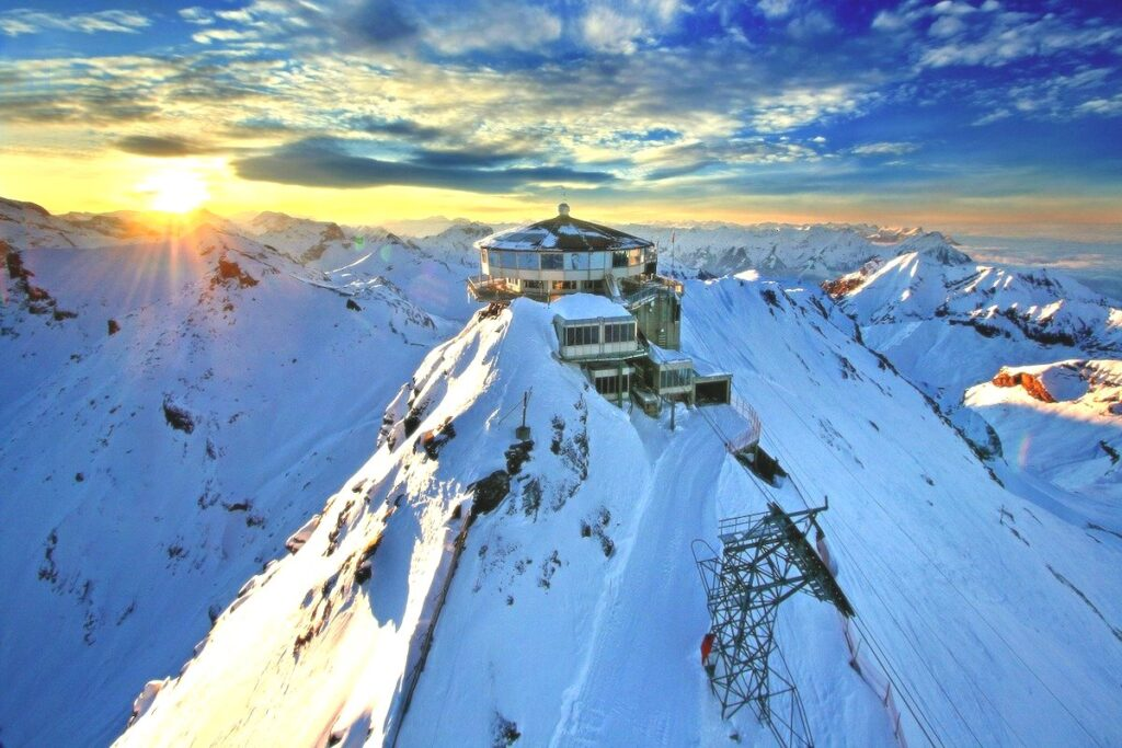 a building perched at the top of a snow covered mountain with the sun setting behind it
