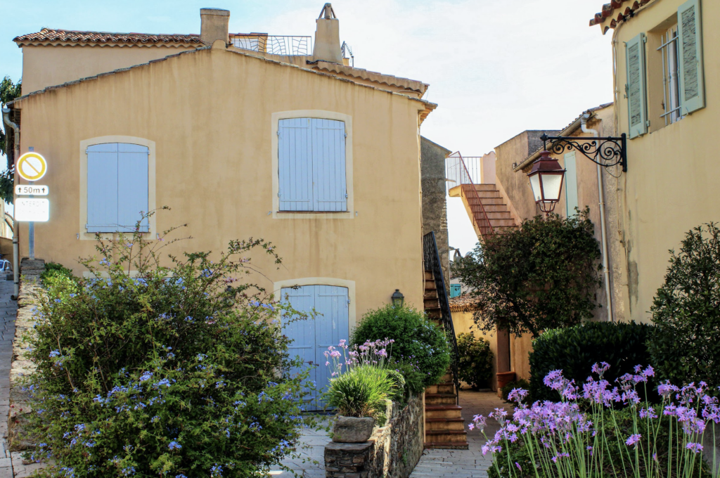 French house in Grasse with blue shutters and purple flowers growing in the garden
