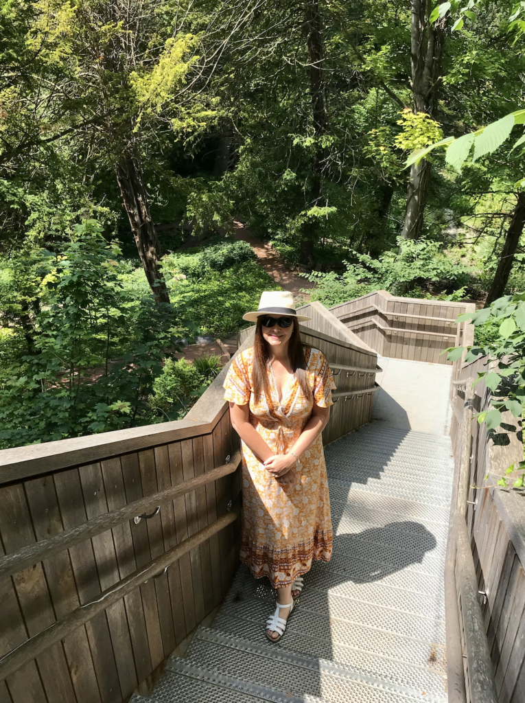 Angie standing on the wooden stairs leading to the Glen