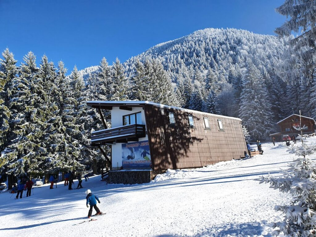 A boy skiing past a chalet in Romania
