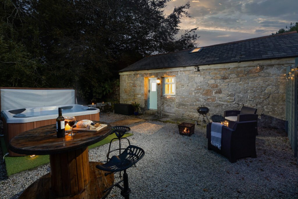 View to side of stone cottage with hot tub , fire pit and patio table in the picture