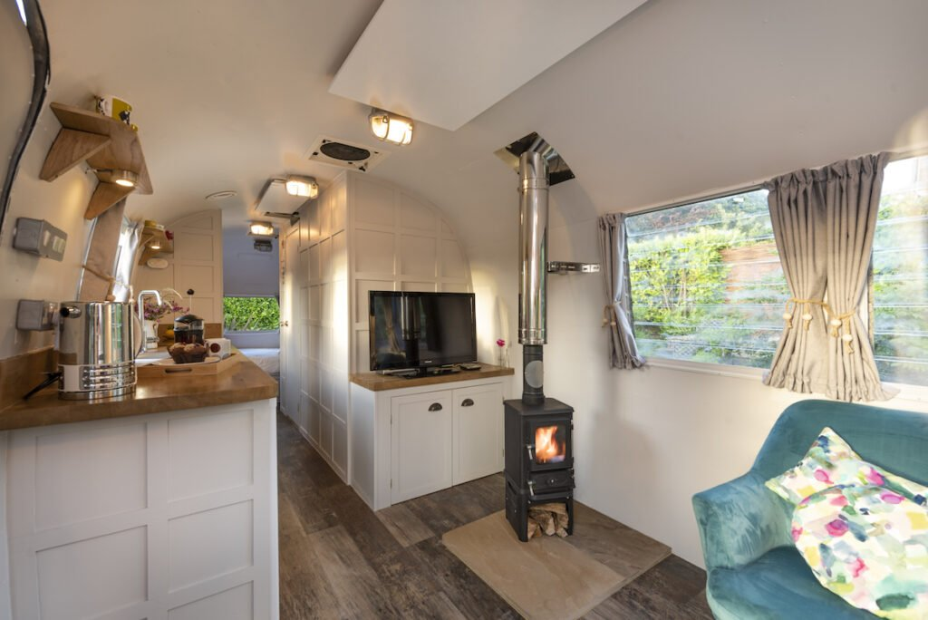 Interior of silver stream featuring kitchen area with wood burner and turquoise chair