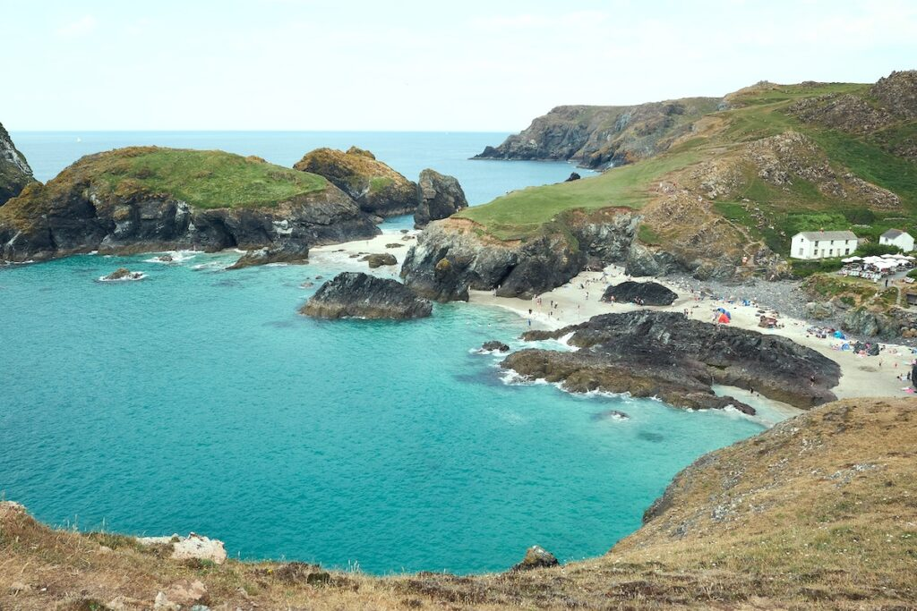 Turquoise blue waters of Kynance Cove with a White House on the clifftop