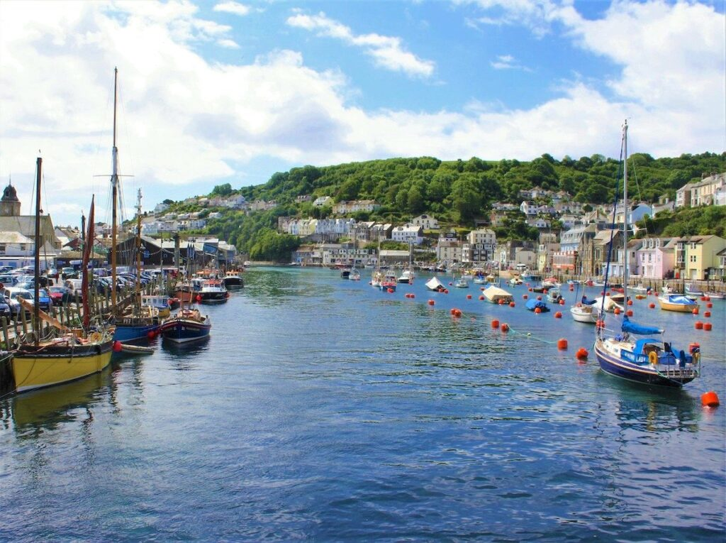 fishing boats in Looe harbour with a view of pastel coloured houses in the distance