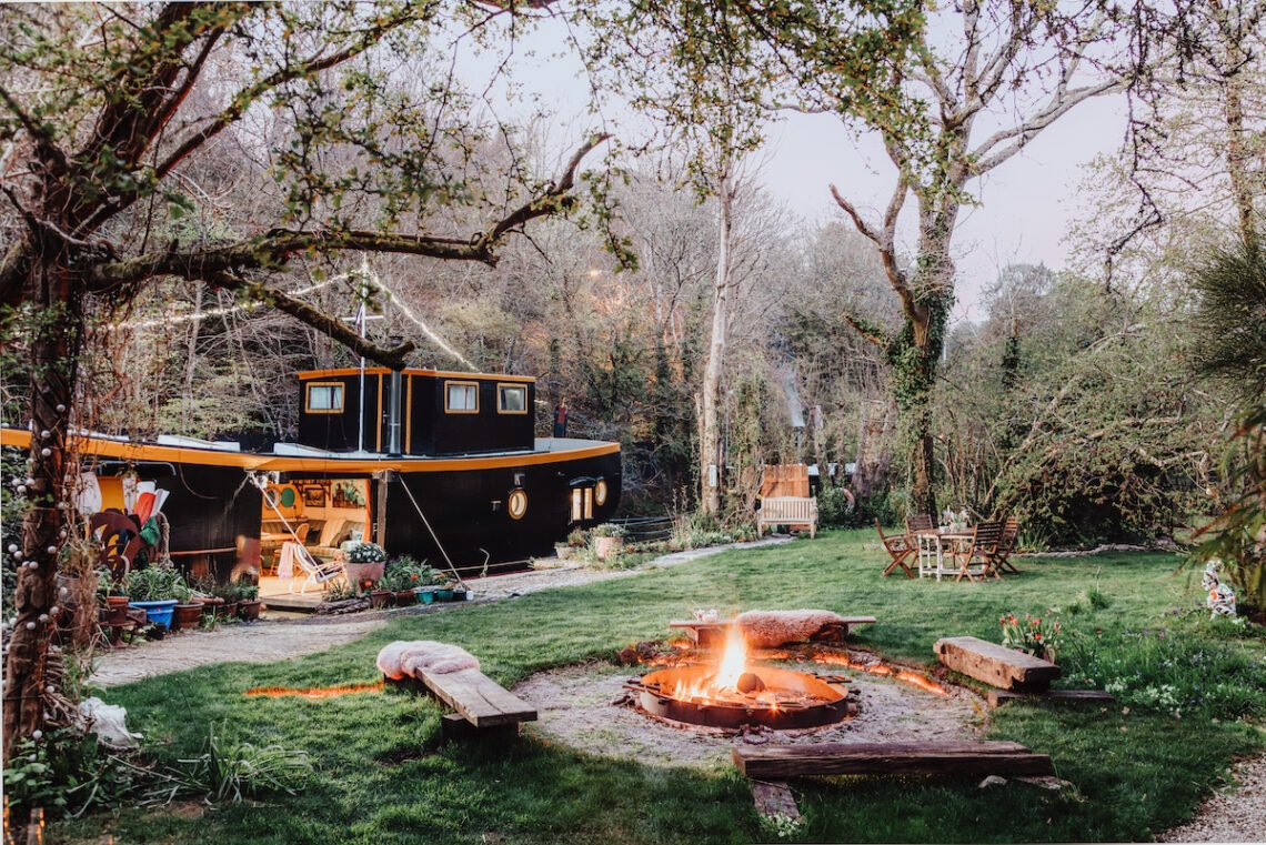Black Houseboat moored beside a grass area with fire pit